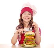 Liten flickakock med den stora hamburgaren som är klar för lunch Royaltyfri Foto