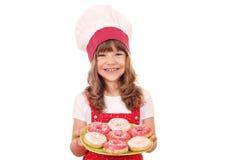 Liten flickakock med donuts Arkivfoto