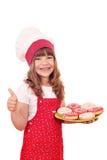 Liten flickakock med donuts och tummen upp Royaltyfri Bild