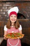 Liten flickakock med pizza i pizzeria Royaltyfri Foto