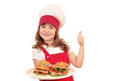 Liten flickakock med smörgåsar och tummen upp Fotografering för Bildbyråer