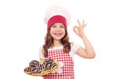 Liten flickakocken med chokladdonuts och oken räcker tecknet Arkivfoto