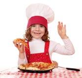 Liten flickakocken med pizza och oken räcker tecknet Arkivfoto