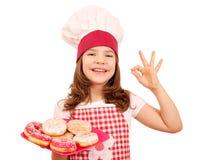 Liten flickakocken med söta donuts och oken räcker tecknet Royaltyfria Bilder