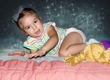 liten flickakrypning på sängen arkivfoto