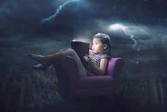 Liten flickaläsning i storm royaltyfri bild