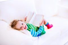 Liten flickaläsning på en soffa royaltyfri fotografi