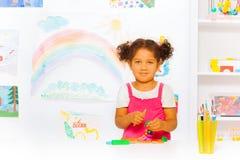 Liten flickalek med att modellera lera i klassrum arkivfoton