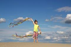 Liten flickalek och vinka med färgrik bandsommarsäsong arkivfoto