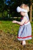 Liten flickalekar med ett sugrör Royaltyfri Foto