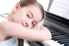 Liten flickalekar på det elektriska pianot. Royaltyfri Foto