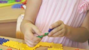 Liten flickalekar som inomhus framkallar leksakformgivaren lager videofilmer