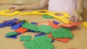 Liten flickalekar som inomhus framkallar leksakformgivaren arkivfilmer