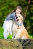 Liten flickalilla flickan omfamnar golden retriever i parkera Fotografering för Bildbyråer