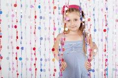 Liten flickalooks ut hänger upp gardiner bakifrån Royaltyfri Bild