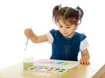 Liten flickamålarfärger med vattenfärger på tabellen royaltyfria bilder