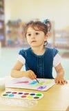 Liten flickamålarfärger med vattenfärger på tabellen royaltyfria foton