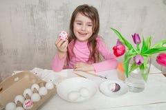 Liten flickamålningägg som förbereder sig för påsk arkivbild