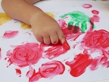 Liten flickamålning vid färg för fingerhandmålarfärg, obegränsad gränslös fantasi till och med färgrika färgläggningaffischer arkivfilmer