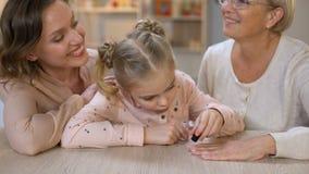 Liten flickamålningfarmodern spikar att göra manikyr, kvinnlig skönhet, fritid stock video