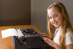 Liten flickamaskinskrivning på den gamla skrivmaskinen Royaltyfri Fotografi
