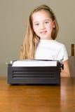 Liten flickamaskinskrivning på den gamla skrivmaskinen Royaltyfri Bild