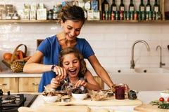 Liten flickamatlagning med hennes moder i köket arkivbilder