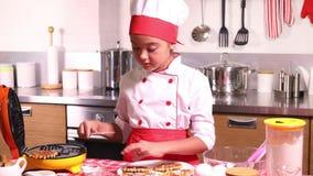 Liten flickamatlagning svamlar i köket hemma stock video