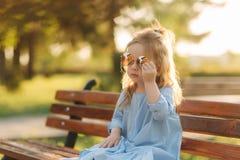 Liten flickamodellen i blått klär, och solexponeringsglas sitter på en bänk i parkera royaltyfria foton