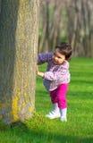 Liten flickanederlag bak ett träd i en skog Royaltyfri Bild