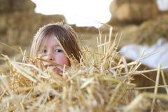 Liten flickanederlag i höet Fotografering för Bildbyråer
