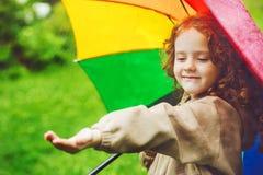 Liten flickanederlag under ett paraply från regnet Royaltyfria Foton