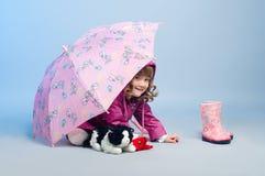 Liten flickanederlag vid paraplyet Arkivbild
