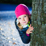 Liten flickanederlaget bak ett träd parkerar in Arkivbild