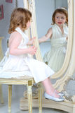Liten flickapåklädden beundrar hennes reflexion i spegel royaltyfri foto