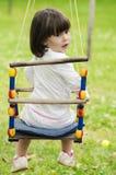 Liten flickaridning på en gunga på en grön bakgrund Royaltyfria Foton