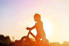 Liten flickaridningcykel på solnedgången, aktivungar Fotografering för Bildbyråer