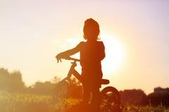 Liten flickaridningcykel på solnedgången, aktivungar Royaltyfri Fotografi