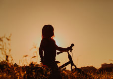 Liten flickaridningcykel på solnedgången, aktivungar Royaltyfri Foto