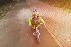 Liten flickaridningrunbike utomhus, ungesport Arkivfoton
