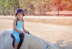 Liten flickaryttare på en vit ponny royaltyfri foto