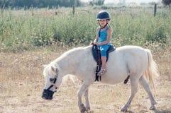 Liten flickaryttare på en vit ponny fotografering för bildbyråer