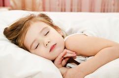 Liten flickasömn i sängen arkivbilder
