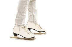 Liten flickas ben i vita isskridskor royaltyfri foto