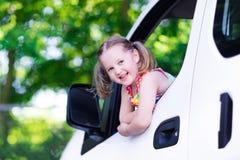 Liten flickasammanträde i den vita bilen arkivfoto