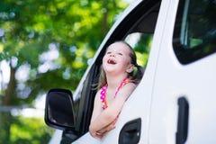 Liten flickasammanträde i den vita bilen royaltyfri bild