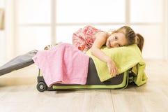 Liten flickasammanträde i en resväska, ordnar till för lopp Arkivfoto