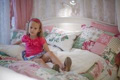 Liten flickasammanträde i en stor färgrik säng Arkivbild