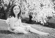 Liten flickasammanträde i gräset Royaltyfri Fotografi