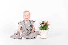 Liten flickasammanträde i grå färgklänning Royaltyfri Bild